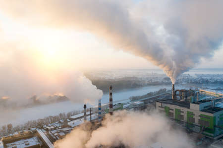 Smoking pipes of thermal power plant against blue sky in winter time. Aerial view. 免版税图像