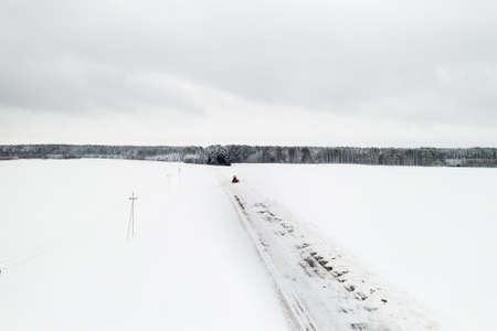 cleaning snow from the streets after a heavy snowfall. Tractor cleans the snow-view from the top.