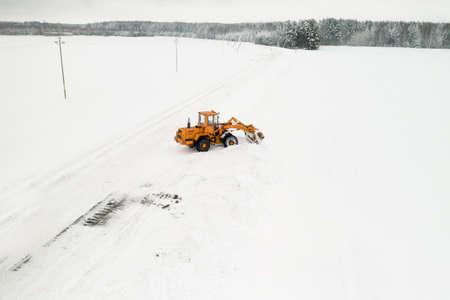 Yellow tractor with a bucket removes snow from the road top view.