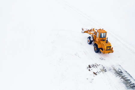 Yellow tractor with a bucket removes snow from the road top view. Banque d'images