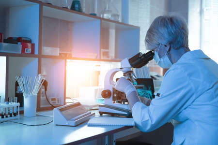 Female medical Doctor or research scientist looking through a microscope in a laboratory.science experiments, laboratory glassware containing chemical liquid for researching biology chemistry samples