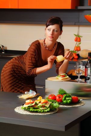 The beautiful woman on kitchen with cheese in a hand Stock Photo