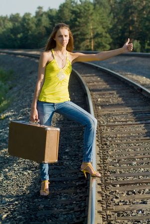 The young woman walks by rail