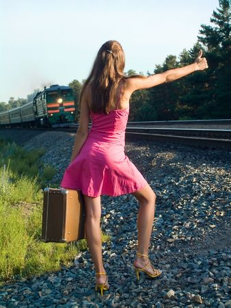 The young woman walks by rail photo