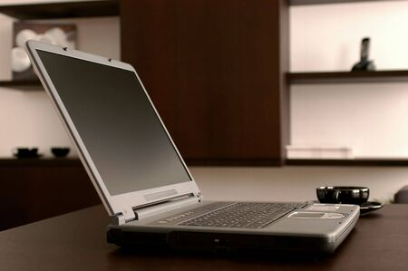 The modern laptop on a dark table                               Stock Photo
