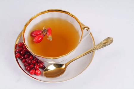Cup with tea and different berries