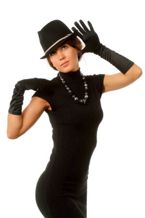 The girl in black clothes on a white background with a hat hat