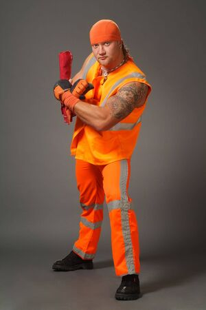 frontlet: The worker in orange clothes on a grey background in studio
