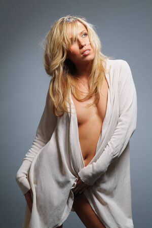 The charming blonde in a light dressing gown on a grey background