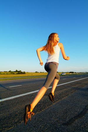 The woman running on road against the sunset sun Stock Photo - 5191390