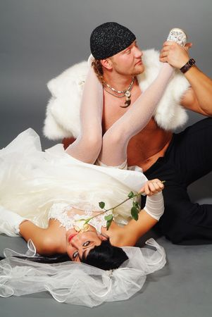 The woman and the man in a wedding dress on a grey background photo