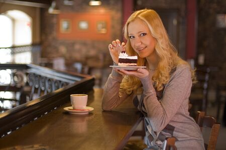 The charming girl drinks coffee with a cake in cafe Stock Photo - 8925825