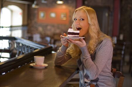 The charming girl drinks coffee with a cake in cafe Stock Photo - 8925824