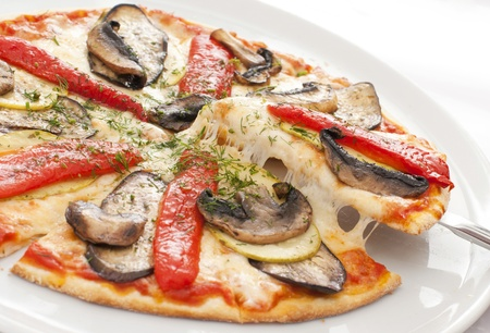 rebanada de pizza: La pizza apetitosa en un plato blanco Foto de archivo