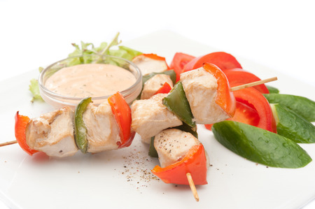 chicken kebab with vegetables and sauce on a white plate