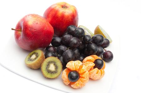 kiwi grapes mandarin apple on a white plate