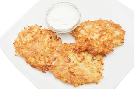 potato pancakes with sour cream on a white plate Stock Photo