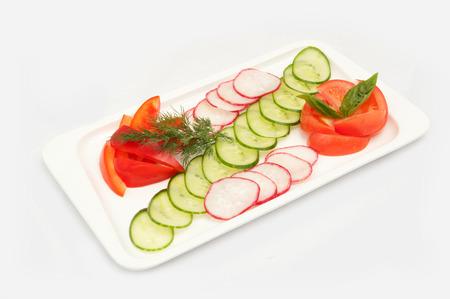 cucumber radish tomato on white plate Stock Photo