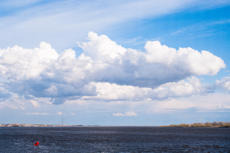 Beautiful clouds over a large river. Red Tank Stock Photo