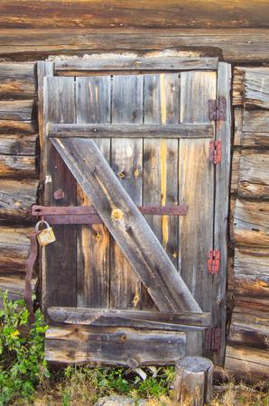 Old wooden door with door lock in an abandoned wooden house Stock fotó