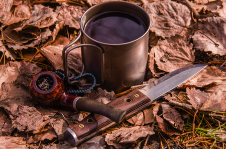 Hiking knife, smoking tube and coffee mug on the background of dry leaves