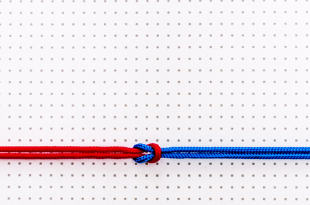 Red and blue ropes knotted with a knot on a light background Stock Photo