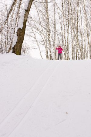 5 year old girl cross-country skiing, sliding down hill photo