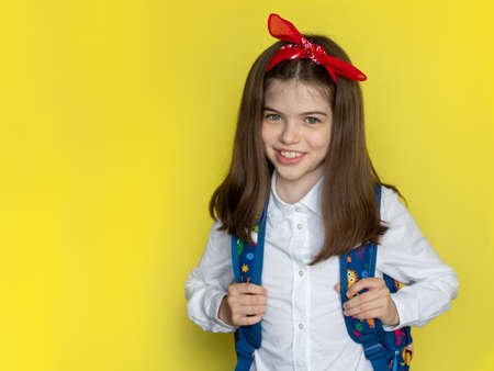 Little beautiful smiling school girl in a school uniform with a backpack. Advertising concept back to school, September 1st, school sale. Portrait on a yellow background