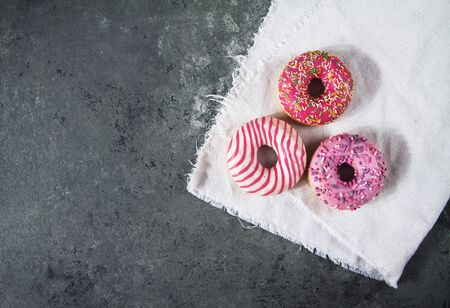 Baked sweet delicious donuts with pastry crumb on gray concrete background. Food texture