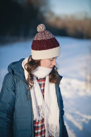 the beautiful young girl in a warm cap from wool of the alpaca in the winter forest. knitting