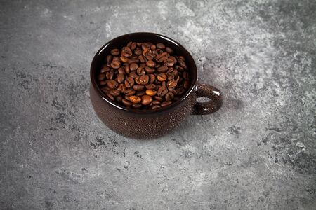 minimalism composition of a round brown ceramic Cup with coffee beans on a gray concrete background