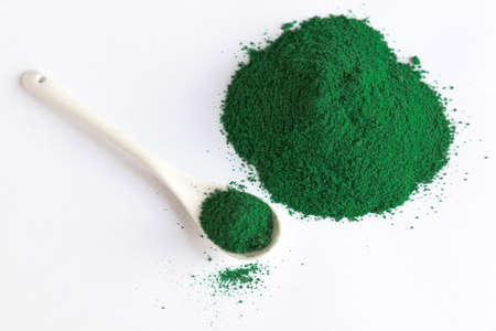 white spoon with Heap of chlorella or spirulina algae, or matcha, on light background. Superfood concept powder. Stock Photo