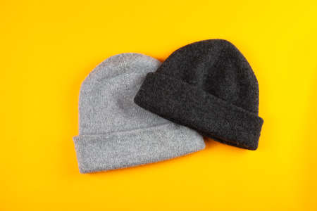 two gray wool Knitted hats on yellow background. spase for text