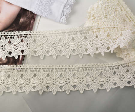 Tapes of ecru white guipure, beauty silk lace fabric on light background. Elastic material. Using for Atelier and needlework store. Flat lay style