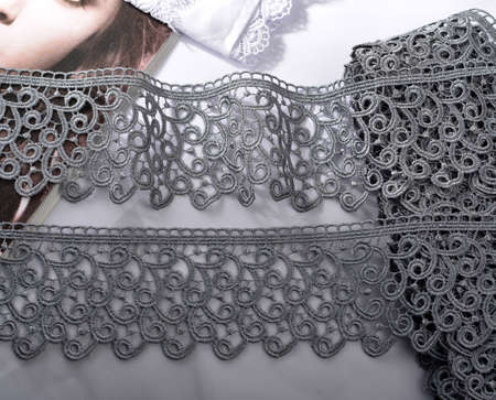 Tapes of gray gentle guipure, beauty lace fabric on light background. Elastic material. Using for Atelier and needlework store. Space for text