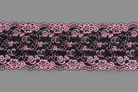 pink black color straight strip of lace fabric on gray background. Elastic silk nylon braid border. use clothes linen decoration. repeating pattern and interweaving threads. texture for websites