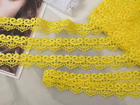 Tapes of yellow gentle guipure, beauty lace fabric. Elastic material. Using for Atelier and needlework store. Space for text. repeating pattern and interweaving threads. texture for websites Stockfoto