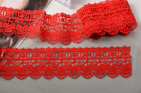 Tapes of red gentle guipure, beauty lace fabric. Elastic material. Using for Atelier and needlework store. Space for text. repeating pattern and interweaving threads. texture for websites