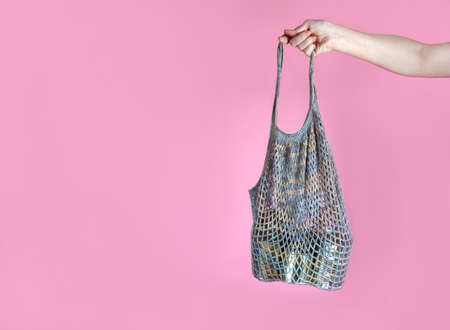woman's hand holds a gray crochet string bag with tin cans, humanitarian aid, food donation, on a pink background. Space for text Foto de archivo