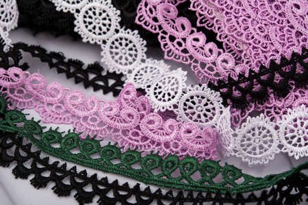 pile of purple, green, white and black gentle luxury quality guipure, lace fabric. use for sew clothes linen decoration. texture for websites. Space for text.