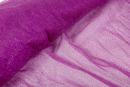 Lightweight pink Crumpled beautifully draped lace festive tulle fabric with sparkles. texture of wedding clothes, veil, dress, skirt. Use for sew fashion industry with copy space. Close up soft focus