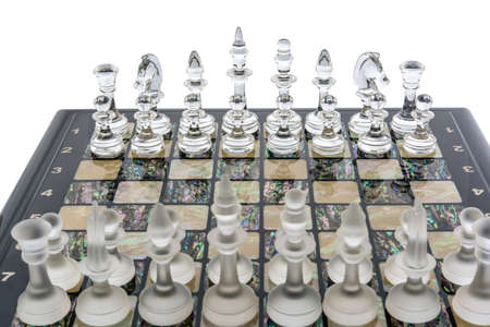 Transparent different glass chess pieces figures standing on pearl board in white. Glossy and matte set of shapes. game concept of confrontation. Stock Photo