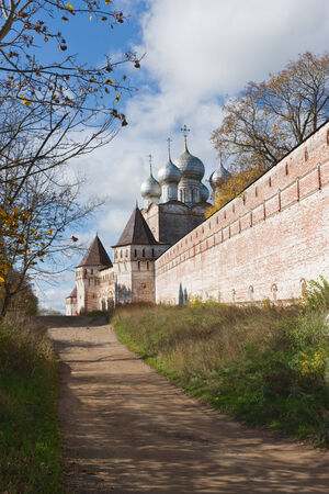 Russia. Beautiful monastery wall and the road stretches into the distance. photo