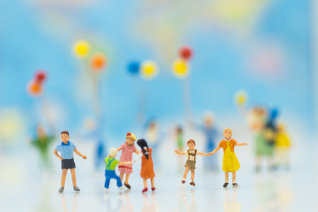 Miniature people: Children play together fun. backdrop is a map of the world, using as background International day of families concept.