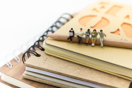 Miniature people, sitting on the pencil and read book on a big book. Image use for background education,or business concept.