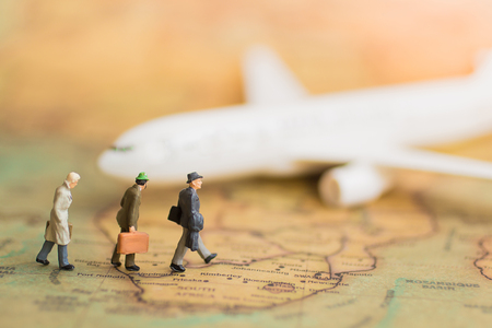 Miniature business people : Businesses team waiting for plane on world map using as background travel, business trip traveler adviser agency or transportation concept. Stock Photo