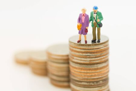 Miniature people, Old couple figure standing on top of stack coins using as background retirement planning, Life insurance concept.
