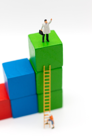 Miniature people: Businessmen take the climbing stairs on a colorful wooden building. Image use for get better position of work.