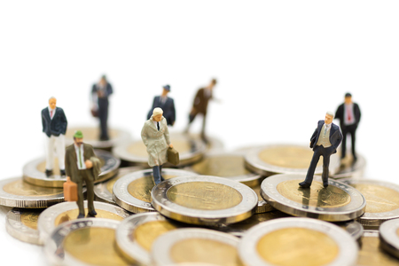 Miniature person: Businessman standing on stack of coins. Image use for business, financial concept.