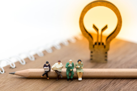 Gente miniatura, sentada en el libro y la idea de la lámpara. Uso de la imagen para educación de fondo, o concepto de negocio. Foto de archivo